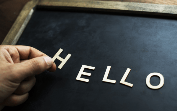 Image of a hand placing letter to spell the word 'hello' onto a chalk board
