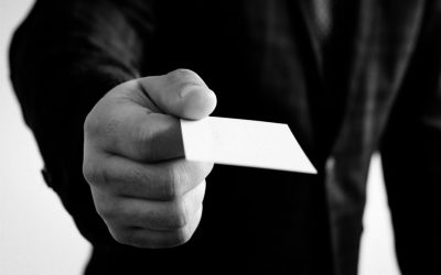 Black and white photo of business man holding a business card out for someone to take