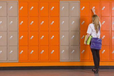 Education - School girl reaching up to open locker in school hallway.